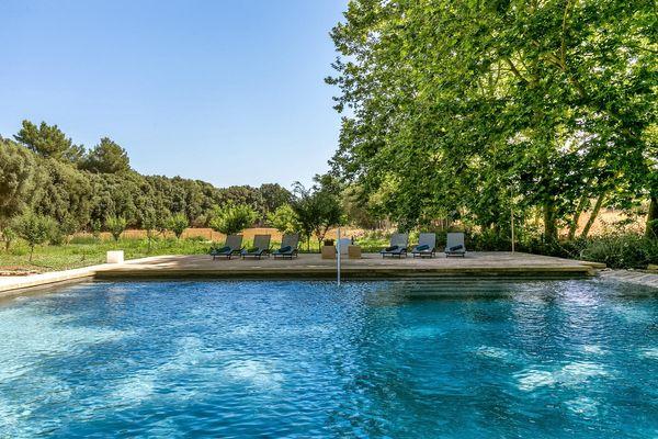 Türkisblauer Pool umrahmt von Bäumchen