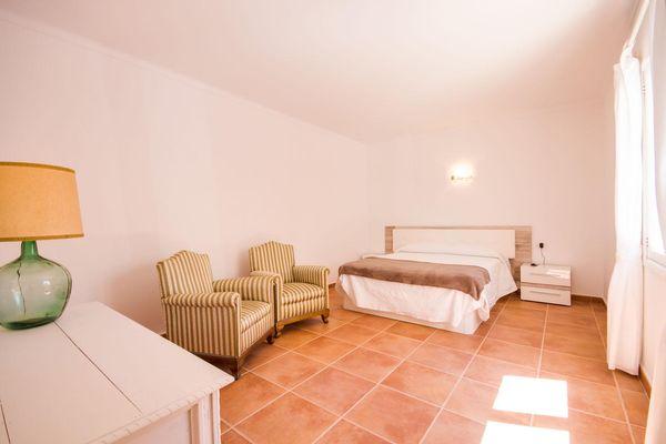 Großes Schlafzimmer mit gemütlichen Polstersesseln