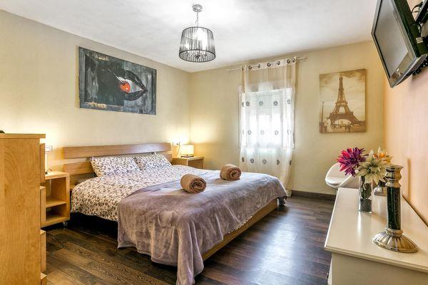 Doppelbettschlafzimmer mit TV und Sessel