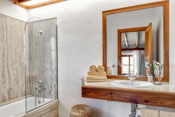 Teilansicht eines Badezimmers mit Blick durch den Spiegel ins Schlafzimmer