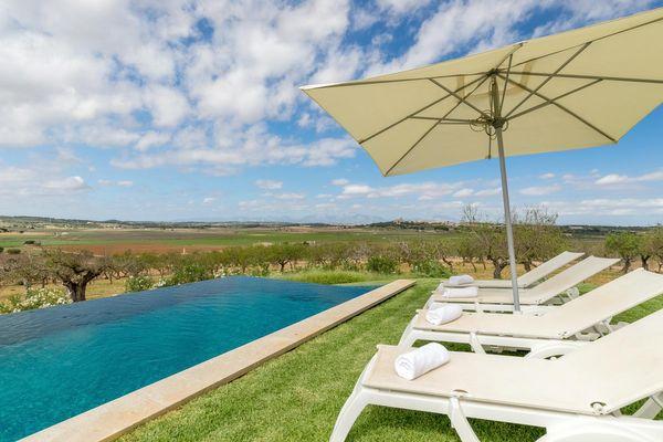 Pool mit Sonnenliegen und freiem Blick in die mallorquinische Landschaft