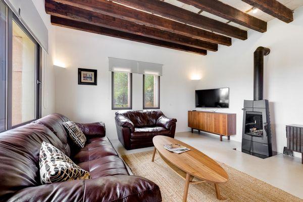 Rustikales Wohnzimmer mit Holzdecken und Kamin