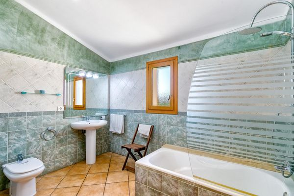 Zweites Badezimmer mit Badewanne und integrierter Dusche