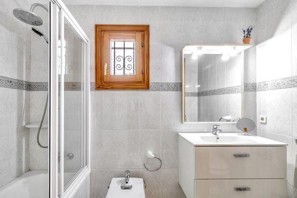 Helles Badezimmer mit Wanne und integrierter Dusche