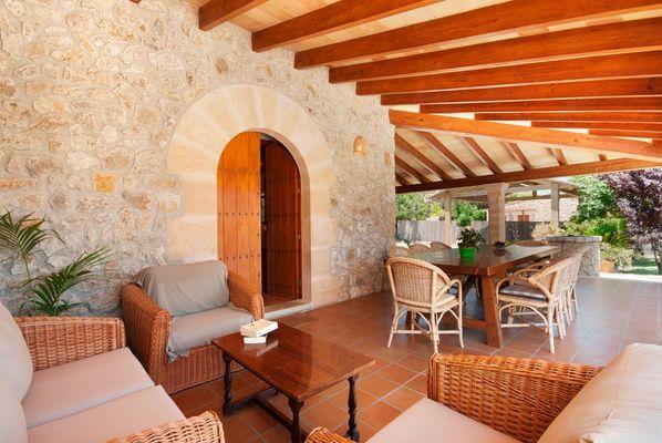 Überdachte Terrasse mit Esstisch und Sofa